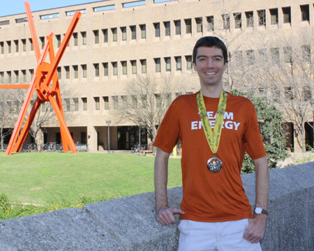 Smith posing with marathon medal outside of School of Engineering building.
