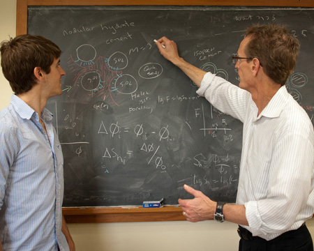 A professor gestures toward diagrams on a chalkboard as student looks on.