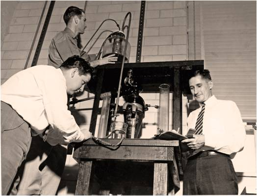 Dr. George Fancher, left, supervises graduate students in the Drilling Fluids Research Lab, 1950s.