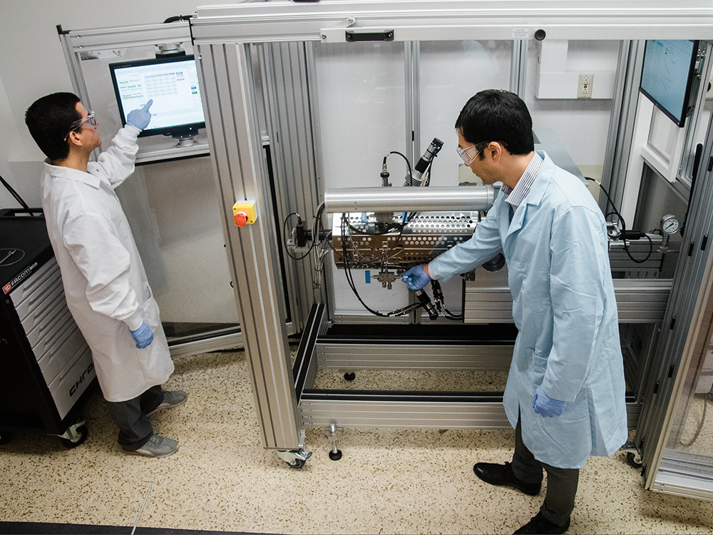 two people in lab with large machine and computer monitor